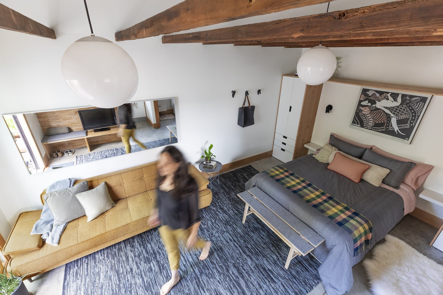 Portland ADU with exposed wood beams, concrete floors, bed and couch