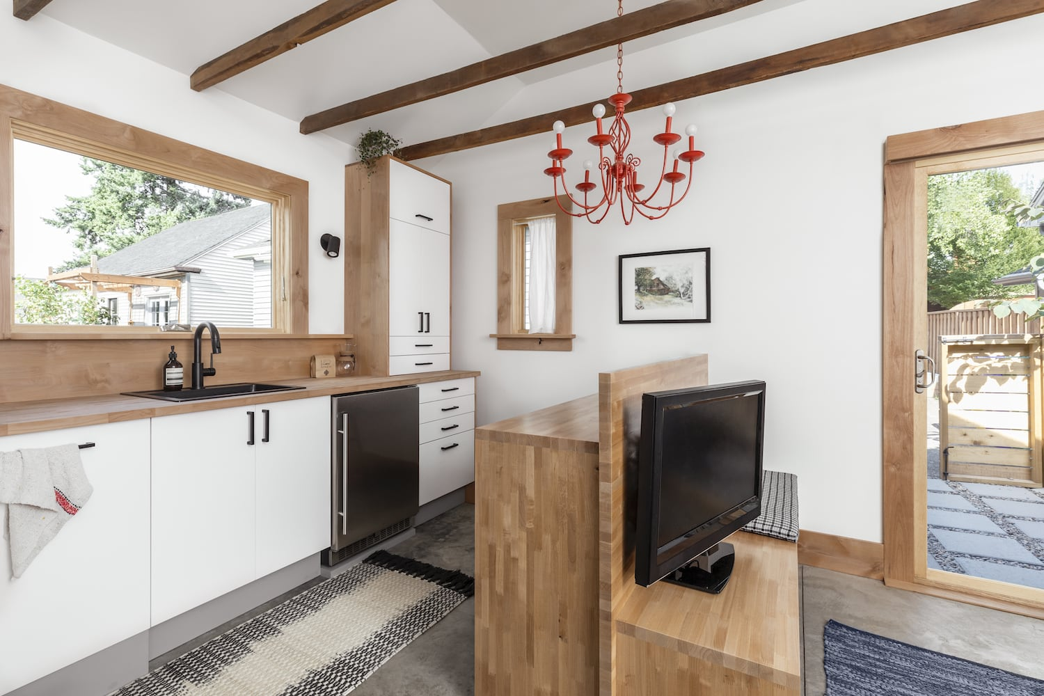 ADU kitchenette with wood peninsula, concrete floors and exposed wood beams