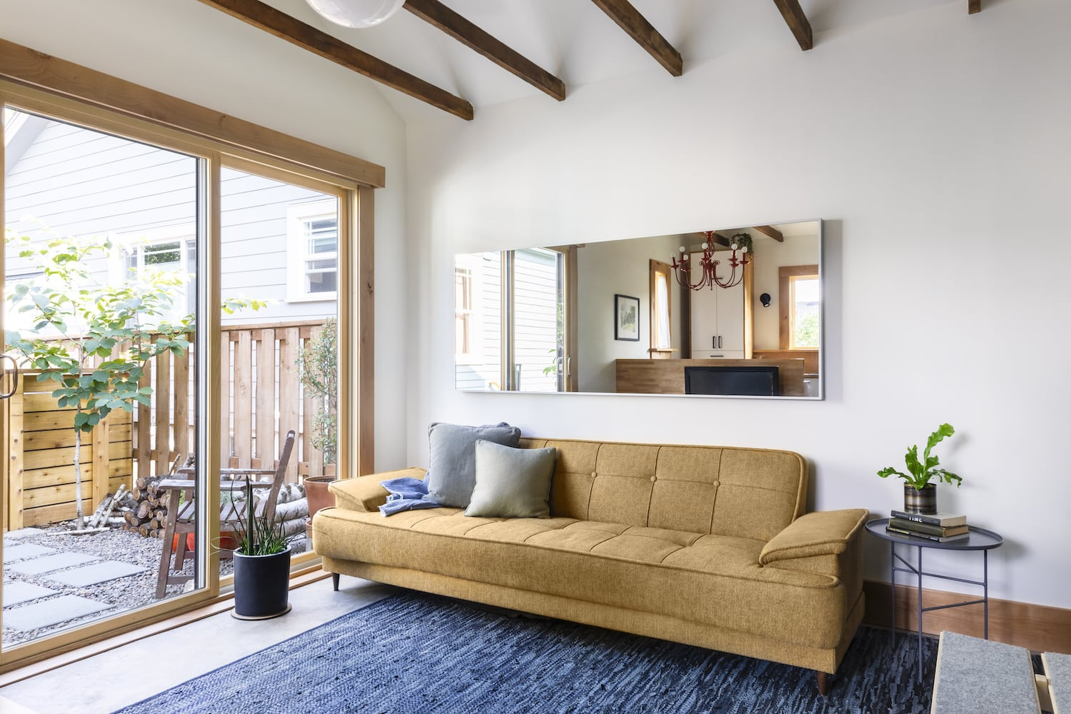 Garage conversion to guest house with couch, sliding doors and natural wood trim
