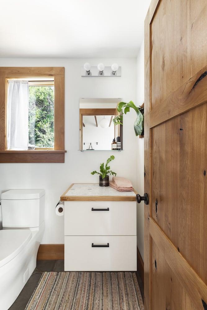 Bathroom with floating cabinet, wood door, wood window trim, concrete floors