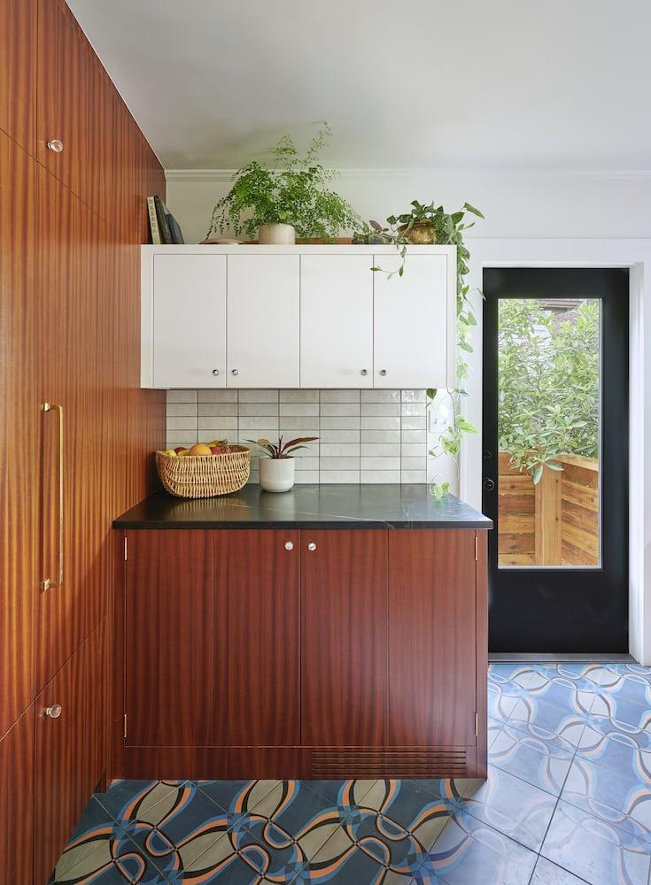 Kitchen with sapele cabinets, white tile backsplash, soapstone countertop