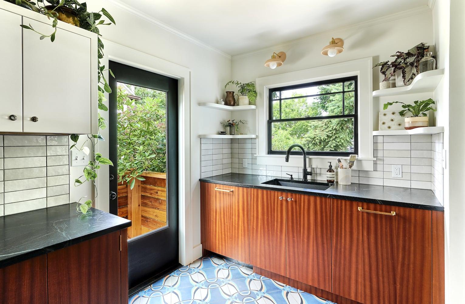 Kitchen with soapstone counters, white tile backsplash, floating shelves