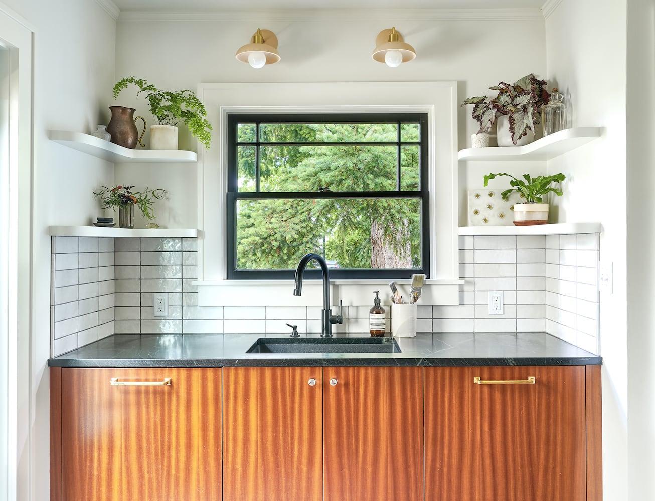 Sink area with black plumbing fixtures, black windows, decorative sconces