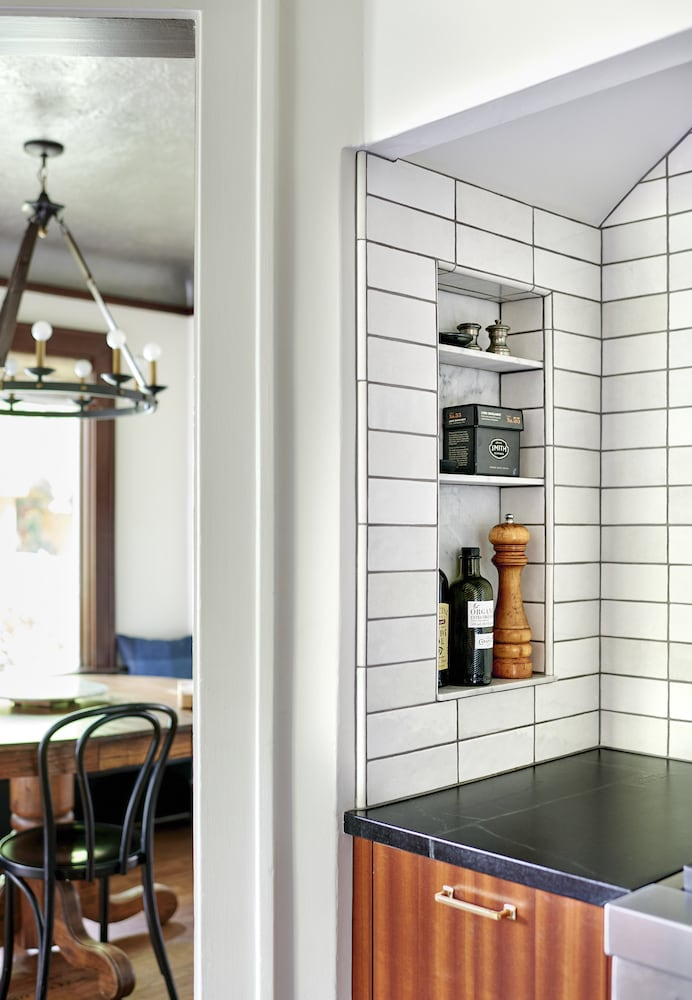 Kitchen spice niche with white tile, soapstone counter, brass hardware, sapele