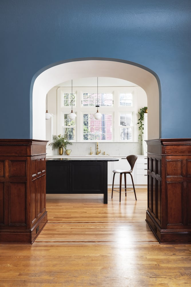 Willamette Heights - view into kitchen from dining room, blue walls, archway, white kitchen, black island