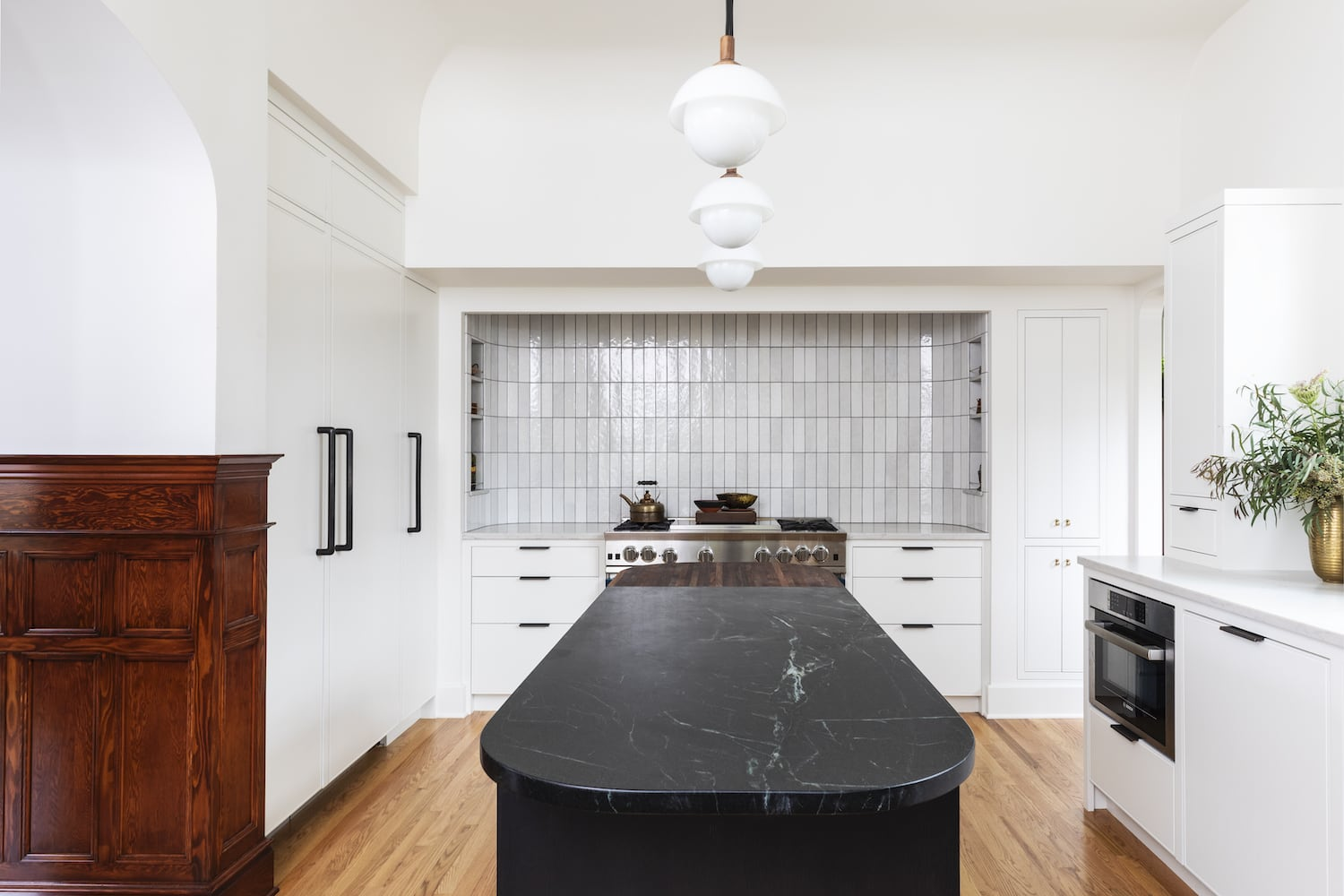 Willamette Heights - traditional white kitchen, black curved island, range alcove, pendant lights