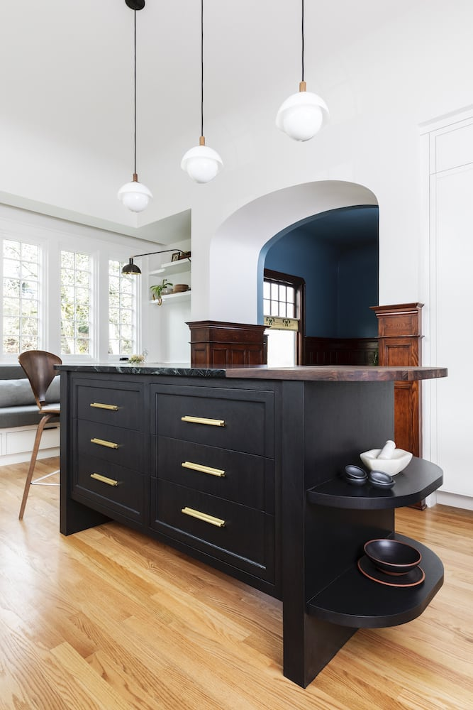 Willamette Heights - traditional kitchen with black curved island, wood floors, blue dining room beyond